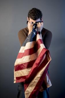 Verticaal schot van een teruggetrokken militair die in verdriet schreeuwt en zijn tranen met de vlag van verenigde staten schoonmaakt