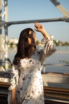 Verticaal schot van een vietnamees meisje dat de zonnestralen van haar gezicht probeert te blokkeren