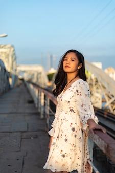 Verticaal schot van een vietnamees meisje dat zich op een oude brug bevindt