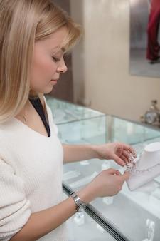 Verticaal schot van een vrouw die diamanten halsband bij juwelierszaak onderzoekt