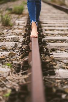Verticaal schot van een vrouw die in spijkerbroek blootsvoets door de treinrails loopt
