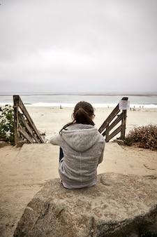 Verticaal schot van een vrouw die op een steen zit en naar de kust kijkt