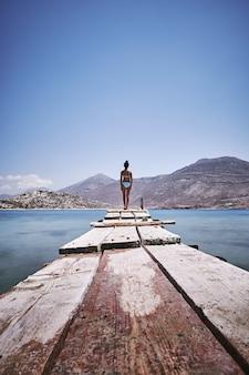 Verticaal schot van een vrouw die zich aan de rand van een houten dok in amorgos-eiland, griekenland bevindt