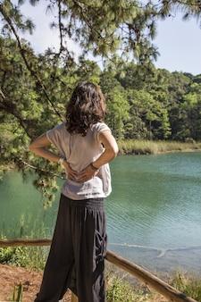 Verticaal schot van een vrouw die zich voor het meer van montebello, chiapas, mexico bevindt