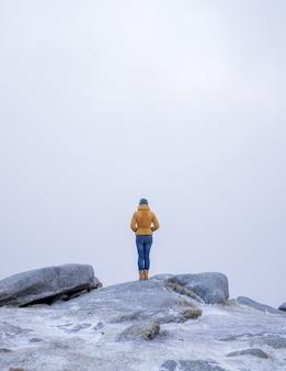 Verticaal schot van een vrouw in een gele jas staande op de steen in de besneeuwde bergen
