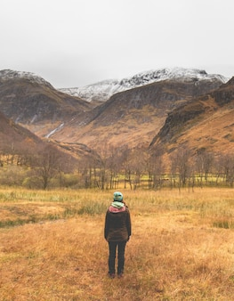 Verticaal schot van een vrouw in een hoed en jas staande in het midden van een veld onder de bergen