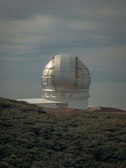 Verticaal schot van een waarnemingscentrum dat op een berg dichtbij een grasrijk gebied voortbouwt