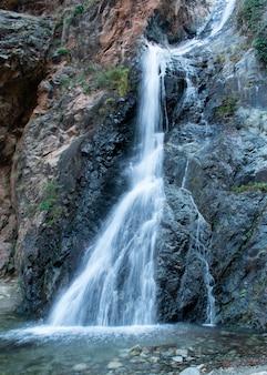 Verticaal schot van een waterval die langs de rotsen komt