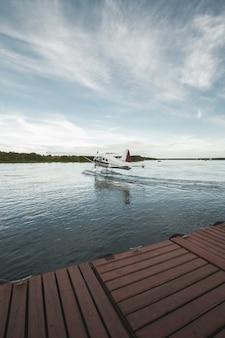 Verticaal schot van een watervliegtuig op het lichaam van een water onder duidelijke blauwe hemel