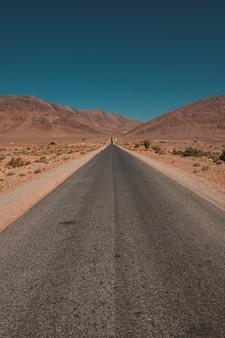 Verticaal schot van een weg in het midden van de woestijn en de bergen die in marokko worden gevangen