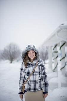 Verticaal schot van een wijfje dat een de winterjas op een sneeuwdag draagt terwijl het glimlachen