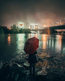 Verticaal schot van een wijfje dat een rode paraplu houdt die zich dichtbij een meer in de stad tijdens nacht bevindt
