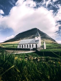 Verticaal schot van een wit huis met grijs dak op groene grasgrond met een berg