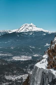 Verticaal schot van een witte berg die door bomen en klippen onder een blauwe hemel wordt omringd