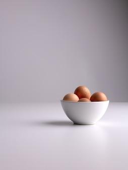 Verticaal schot van een witte kom met bruine eieren daarin op een witte oppervlakte en grijze schone achtergrond