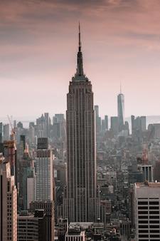 Verticaal schot van een wolkenkrabber die door stadsgebouwen wordt omringd met een mooie hemel