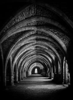 Verticaal schot van gang in zwart-wit bij de crypte bij fountains abbey.