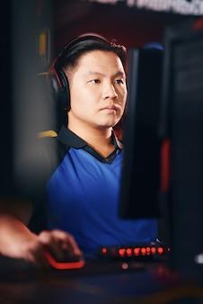 Verticaal schot van geconcentreerde aziatische mannelijke cybersport-gamer die een koptelefoon draagt en naar pc kijkt