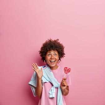 Verticaal schot van gelukkig donkerhuidig meisje kijkt naar boven met blije gezichtsuitdrukking, glimlacht breed en steekt hand op, houdt heerlijke lolly vast, ziet iets geweldigs naar boven, geïsoleerd op roze muur