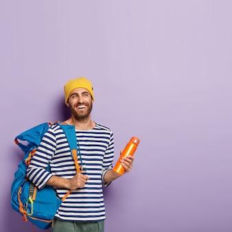 Verticaal schot van gelukkige ongeschoren mannelijke backpacker draagt grote toeristenrugzak, houdt kolf, geïsoleerd over violette muur, vrije ruimte. mensen en toerisme