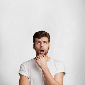 Verticaal schot van geschokte bebaarde man houdt mond wijd open, kijkt verbijsterd naar boven, merkt iets onverwachts op, poseert tegen witte betonnen muur