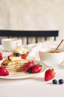 Verticaal schot van gesneden veganistische pannenkoeken met fruit en stroop