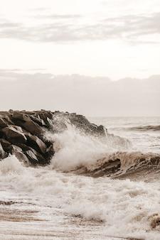 Verticaal schot van golven die op de rotsachtige kust overdag bespatten