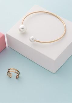 Verticaal schot van gouden met parels armband en dubbele ring op witte en blauwe achtergrond