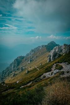Verticaal schot van grasrijke heuvels met rotsen en berg in de verte