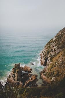 Verticaal schot van grote rotsen in nugget point ahuriri, nieuw-zeeland met een mistige achtergrond