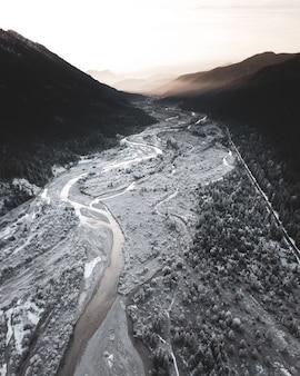 Verticaal schot van halfbevroren rivier die door de bergen stroomt