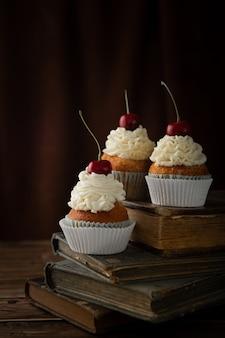 Verticaal schot van heerlijke cupcakes met room en kersen bovenop op uitstekende boeken