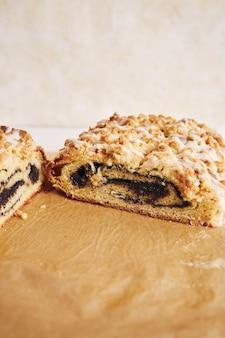 Verticaal schot van heerlijke maanzaadcake met een witte suikerglazuur op een witte tafel