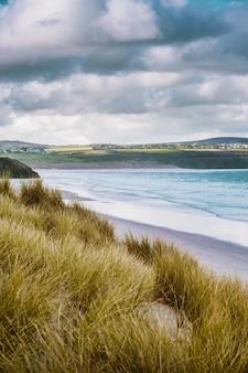 Verticaal schot van het gras behandelde strand door de kalme oceaan die in cornwall, engeland wordt gevangen