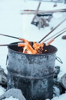Verticaal schot van hotdogs wordt gekookt op een vreugdevuur in een metalen vat in de alpen