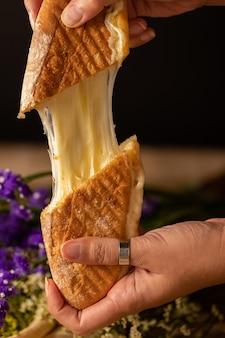 Verticaal schot van iemands handen die twee stukken van een kaassandwich houden