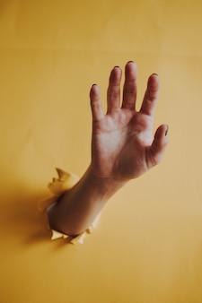 Verticaal schot van iemands handpalm die door een gele document muur breekt