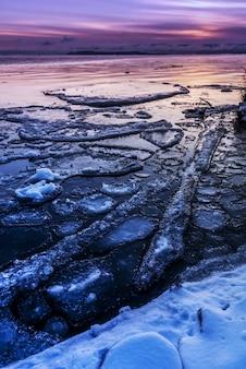 Verticaal schot van ijs en sneeuw op het strand tijdens een zonsondergang