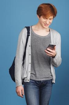 Verticaal schot van jonge knappe gember mannelijke student in grijze kleren en rugzak glimlachen, babbelend met vriend door smartphone op weg in universiteit. moderne levensstijl