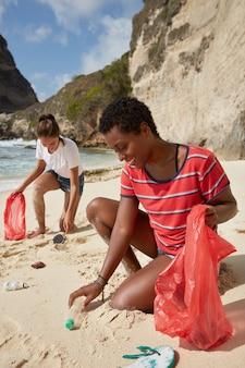 Verticaal schot van jonge multi-etnische actieve vrijwilligers met vuilniszakken schoon kustgebied