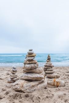Verticaal schot van kiezelstenen op elkaar gestapeld in een balans op het strand