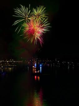 Verticaal schot van kleurrijk vuurwerk dat 's nachts over water in een stad nadenkt