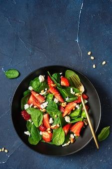 Verticaal schot van kleurrijke verse salade met aardbeien, spinazie en feta