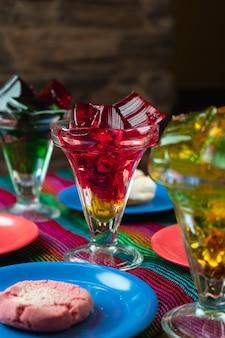 Verticaal schot van kleurrijke zoete gelei-desserts naast koekjesplaten