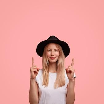 Verticaal schot van knappe jonge vrouw met lang haar, gekleed in elegante hoed en vest, wijst naar boven met beide wijsvingers