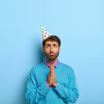 Verticaal schot van knappe jongen met verjaardag hoed poseren in blauwe trui