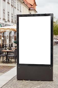 Verticaal schot van leeg reclamebord staat op pavemenet tegen de achtergrond van de stad in de buurt van terrasjes