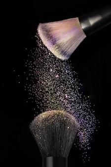 Verticaal schot van make-upborstels op zwart oppervlak