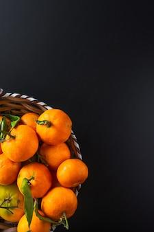 Verticaal schot van mandarijnen met groene bladeren op zwart