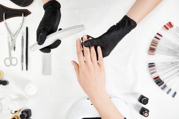 Verticaal schot van manicure het indienen van spijkers met nagelvijl.